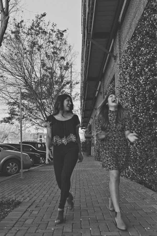 sisters walking down the street laughing
